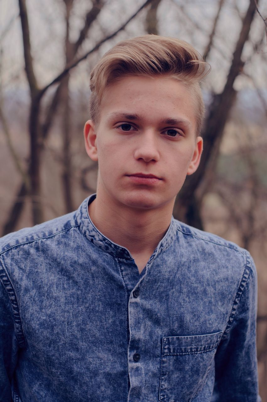 portrait, real people, one person, looking at camera, casual clothing, front view, boys, childhood, leisure activity, lifestyles, outdoors, day, headshot, close-up, blond hair, young adult