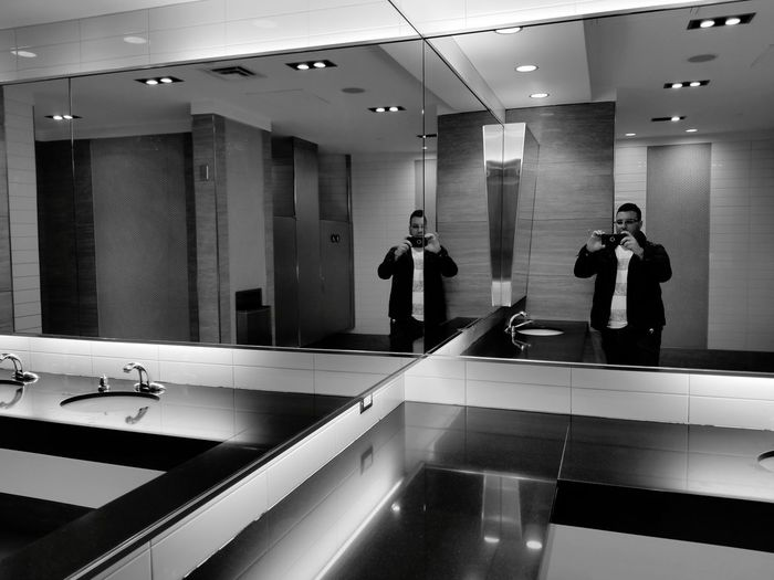 Man Reflecting On Mirror While Photographing With Phone In Bathroom