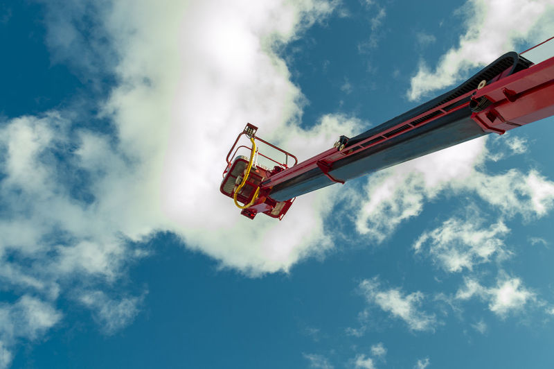 Low angle view of hydraulic platform against cloudy sky