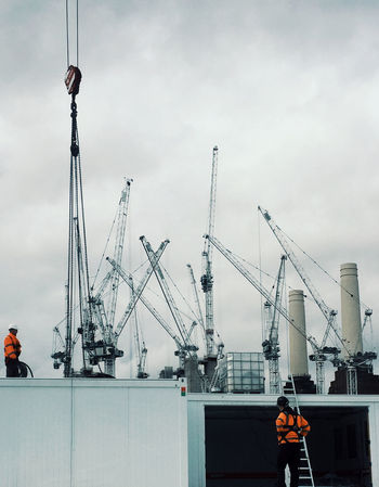 Building in progress Machinery Sky Crane - Construction Machinery Real People Men Two People Industry Construction Industry Architecture Nautical Vessel Nature Transportation Day People Construction Site Development Cloud - Sky Lifestyles Built Structure Commercial Dock Outdoors