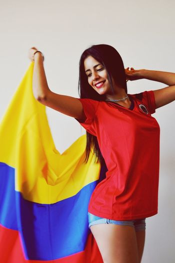 Beautiful Woman With Colombian Flag Against Gray Background
