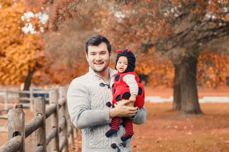 Portrait of smiling father carrying cute daughter while standing in park during autumn
