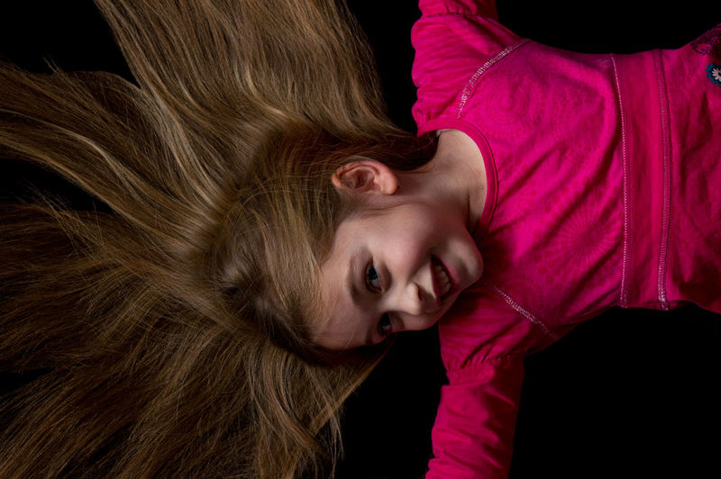 Directly above view of cheerful girl with blond hair lying on black background