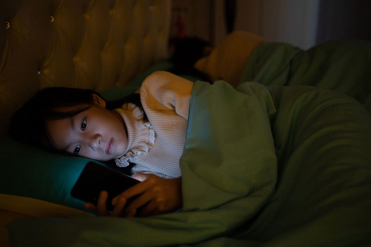 Girl using mobile phone while lying down on bed
