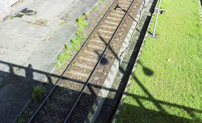 High angle view of railroad tracks on field during sunny day