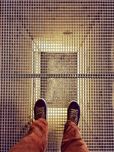 Low Section Of Man Standing On Metal Grate
