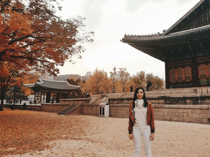 Portrait of woman standing against temple during autumn