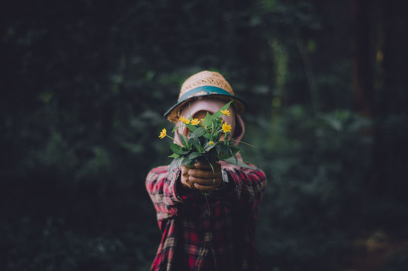 Woman with obscured face holding flowers and leaves