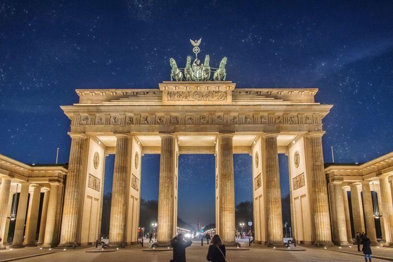 Illuminated brandenburg gate against star field