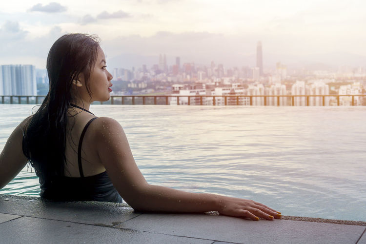 Young woman relaxing in infinity pool against cityscape