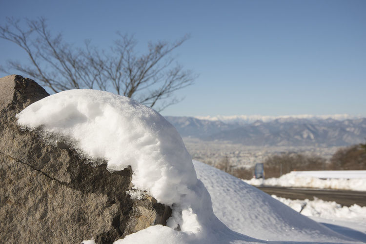 Close-up of snow on landscape against sky