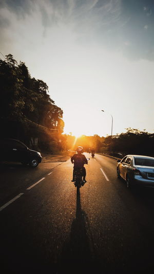 Man on road against sky during sunset