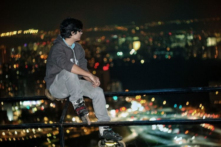 Young man sitting on railing and looking at illuminated cityscape during night