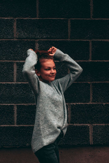 Moody portrait of girl who looks away from camera, standing against brick wall.