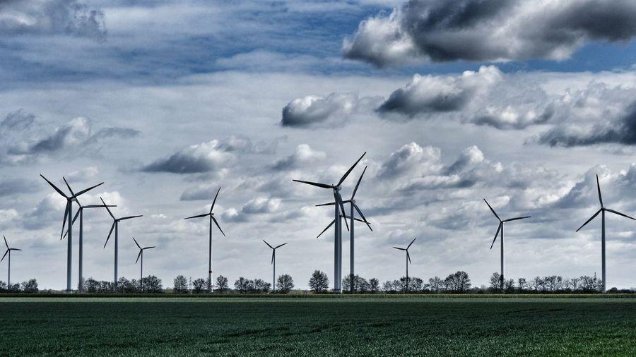 Windmills on field against sky