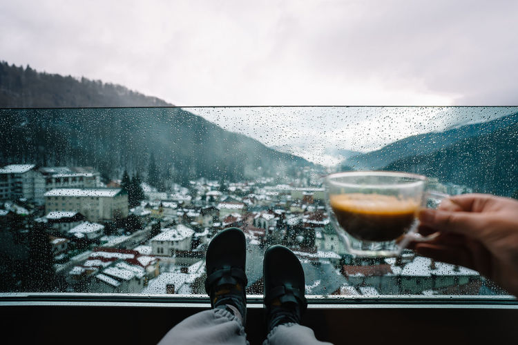 Low section of woman with drink in balcony at mountains against sky