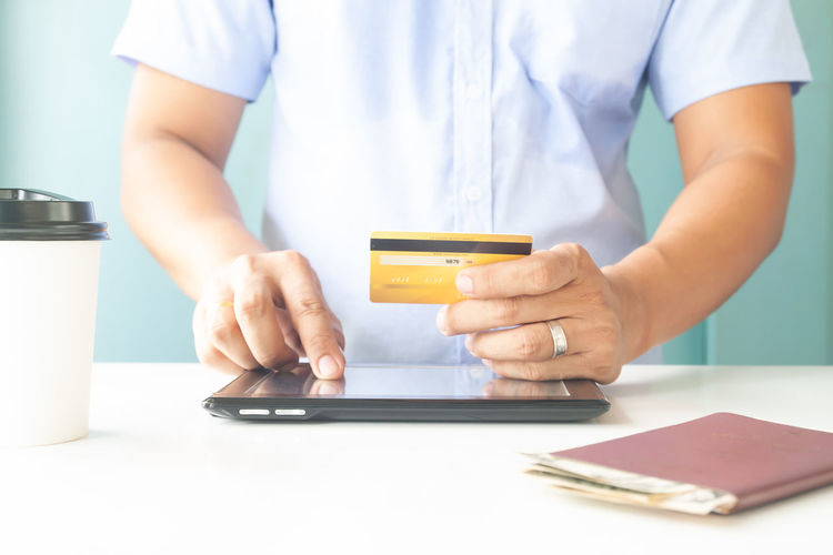 Man hand holding plastic credit card and using tablet. E-payment, business and online payment Hotel Trip Passport Cart Traveler Plastic Concept Entering E-commerce Cvv Ordering Wireless Tax Male Order Debit Smart Security Man Typing RISK Information Data Lifestyle White Phone Ecommerce Keyboard Notebook Finance Electronic Internet Store Home Buy Technology Commerce Banking Using Purchase Business Pay Computer Shopping Laptop Holding Payment Online  Card Credit