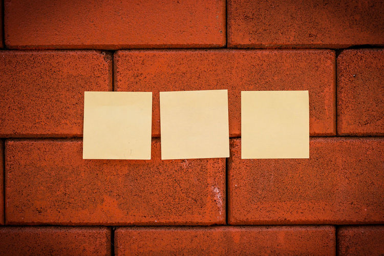 Blank yellow notes on brick wall
