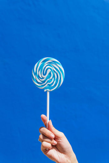 Hand holding ice cream against blue sky