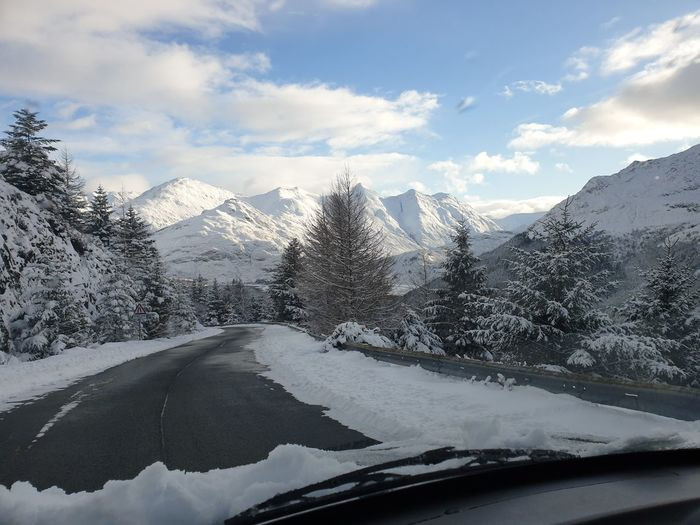Road by snowcapped mountains against sky seen through car windshield