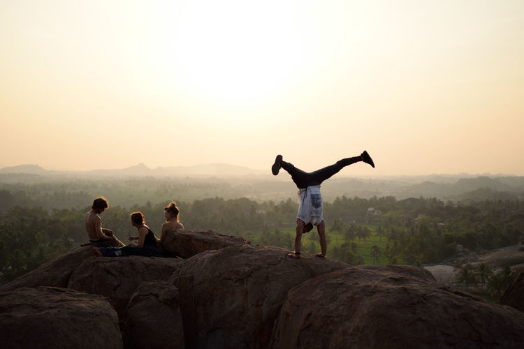 Man doing handstand by friends on rock against sky