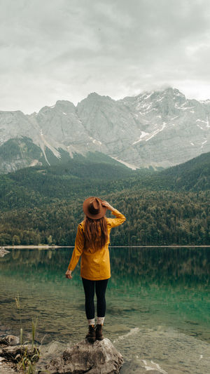 Full length of woman standing on mountain by lake against sky