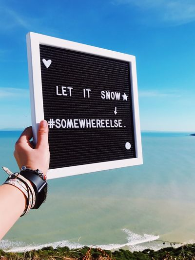 Let It Snow Sea Sun Beach Sea Sun  Holiday Traveler Travel Let It Snow Somewhere Else Winter Hate Winter Summer Summer Time  Hand Human Hand Sky One Person Text Human Body Part Communication Holding Real People Western Script Sign Day Nature Sea Lifestyles Time Leisure Activity Unrecognizable Person
