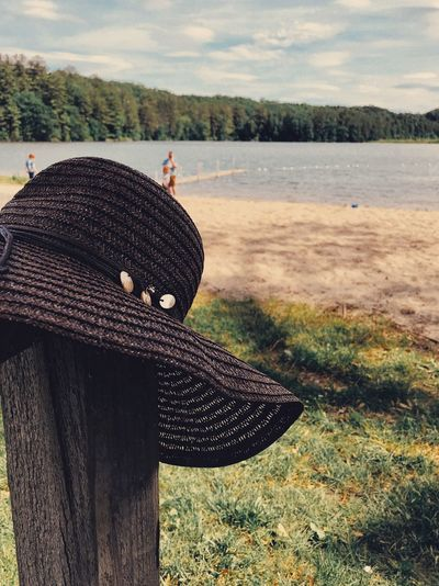 Sun hat at the beach Sun Hat Hat Beach Lake Sand Lake View Lakeshore Sky And Clouds Sunlight Lakeside Hat Water Clothing Nature Plant Day Focus On Foreground Land Sky Lake Outdoors Creativity Beauty In Nature Tranquility Cloud - Sky Tranquil Scene