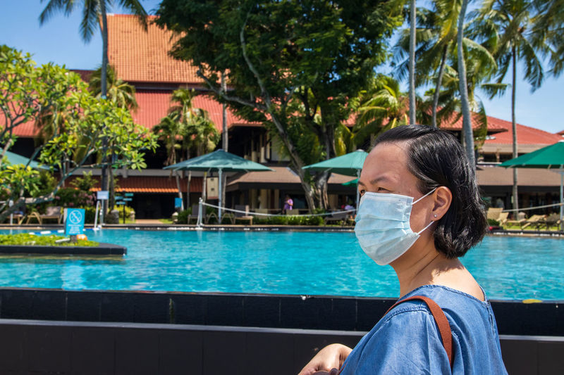 Woman wearing mask looking away while standing by swimming pool