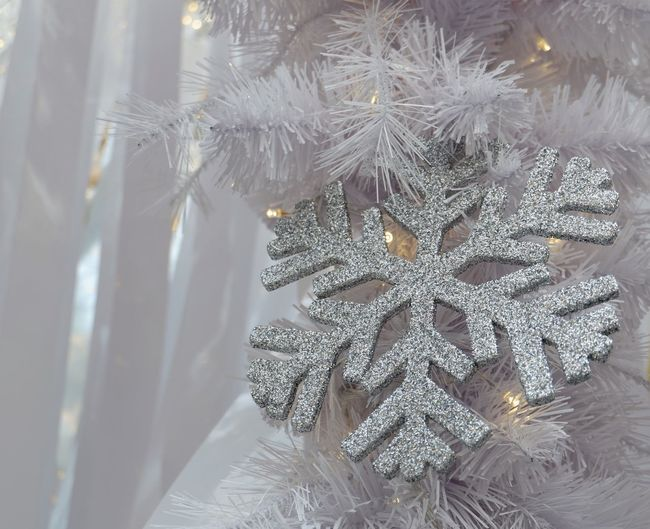 Sparkling silver snowflake with yellow light hangs from Christmas tree for background Modern White Loght Bright Decoration Holiday Festive Silver  Sparkle New Year Winter Decoration Ornament Celebration Close-up Christmas Indoors  Christmas Decoration Christmas Ornament No People Tradition Snowflake Winter Snow Day