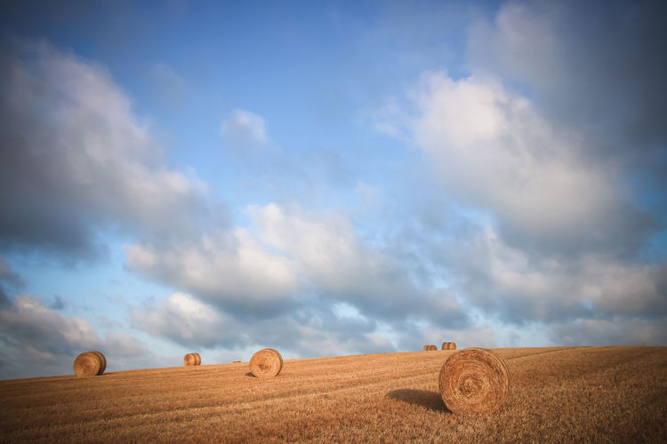 Hay bales on field against sky