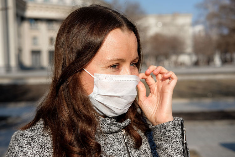 Close-up of woman wearing mask outdoors during winter