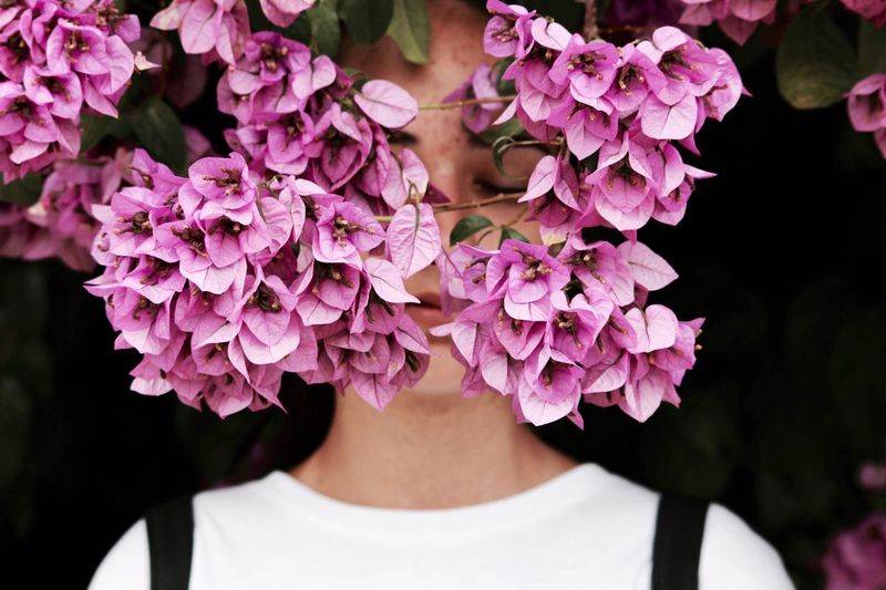 Close Up Of Young Woman With Eyes Closed Standing Pink Flowers
