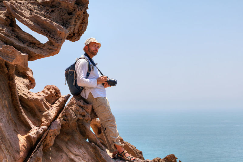 Man with camera on rock formation against sea and sky