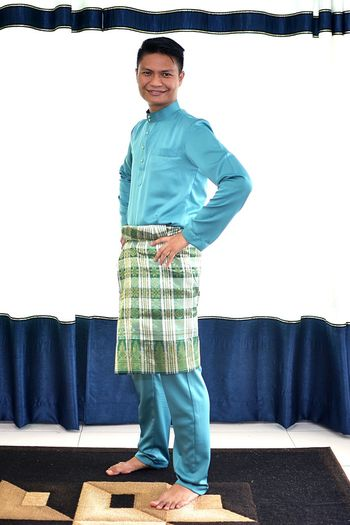 Portrait of man wearing traditional clothing while standing against curtain during eid