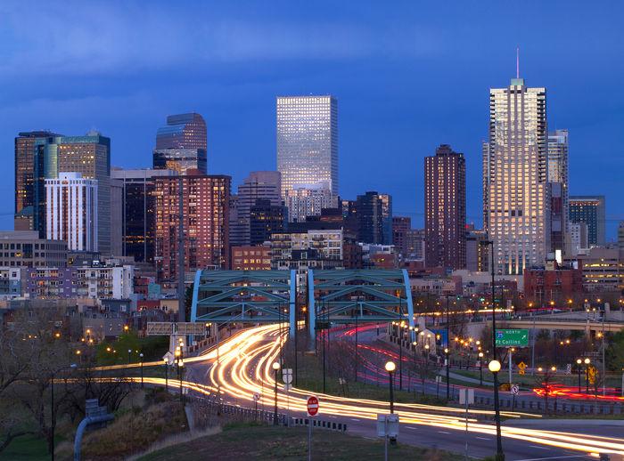 Illuminated Cityscape Against Blue Sky At Night