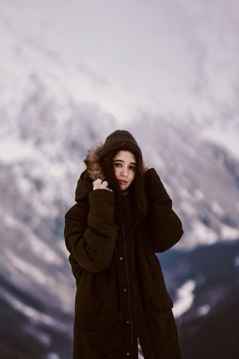 Portrait of young woman standing in snow