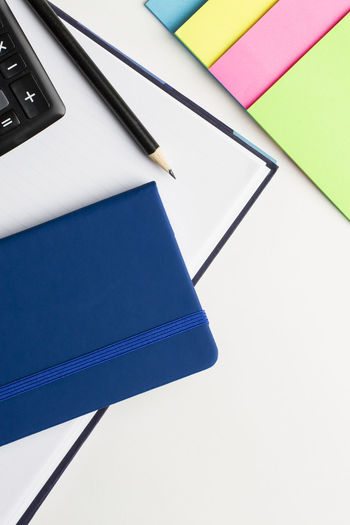 Agenda and notebook with pencil, calculator and notepad on white background. Adhesive Note Blank Blue Book Close-up Education Group Of Objects High Angle View Indoors  Multi Colored No People Note Pad Office Office Supply Paper Pen Publication Small Group Of Objects Still Life Table Two Objects White Background Writing Instrument