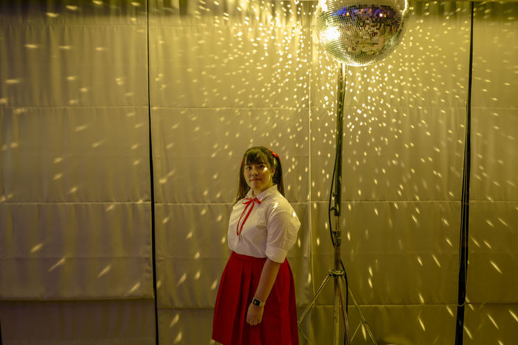 Portrait of woman standing by disco ball