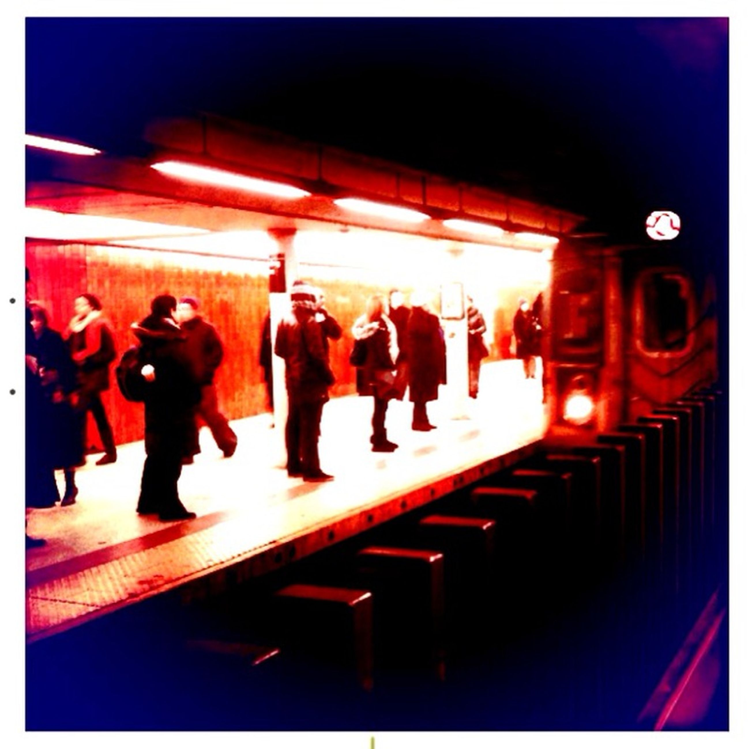 indoors, transfer print, illuminated, auto post production filter, lifestyles, men, leisure activity, person, night, standing, lighting equipment, full length, large group of people, subway station, red, walking, group of people, medium group of people