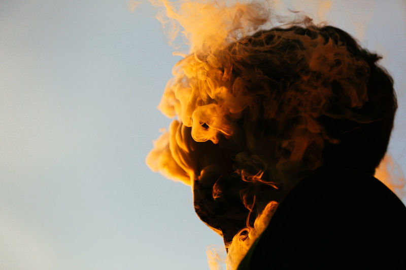 Close-up of person smoking against clear sky