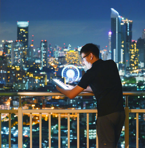 Man using digital tablet while standing in balcony at night