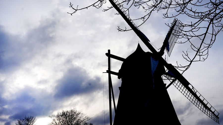 Low angle view of silhouette windmill against sky