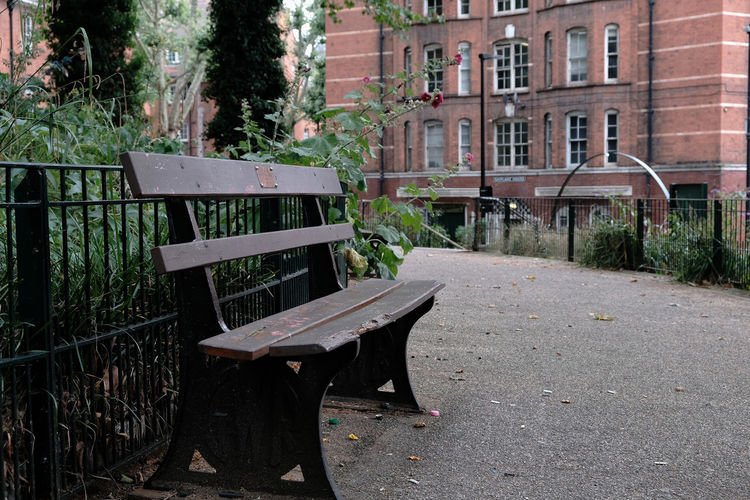 Empty bench and tables in park against buildings in city