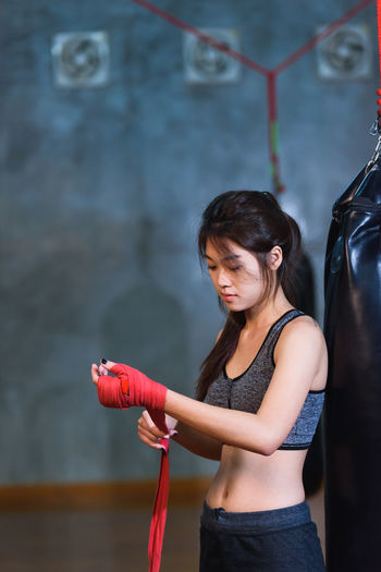 Female boxer wrapping strap on hand while standing against wall
