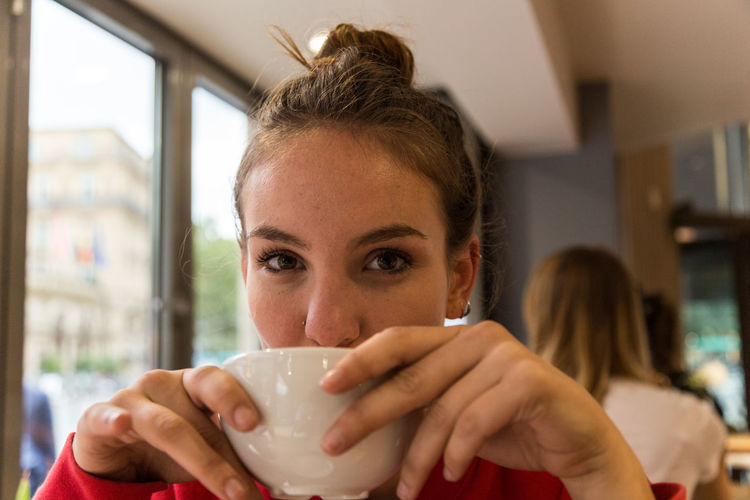 Portrait of young woman drinking coffee at cafe