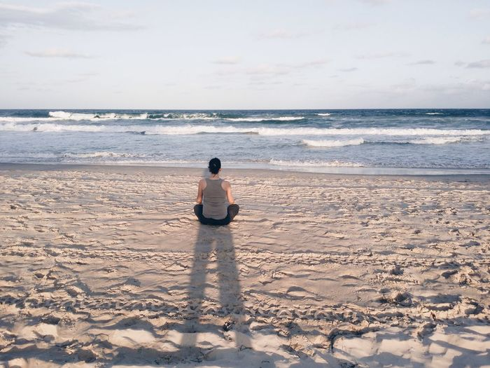 Rear View Of Woman Doing Yoga At Beach