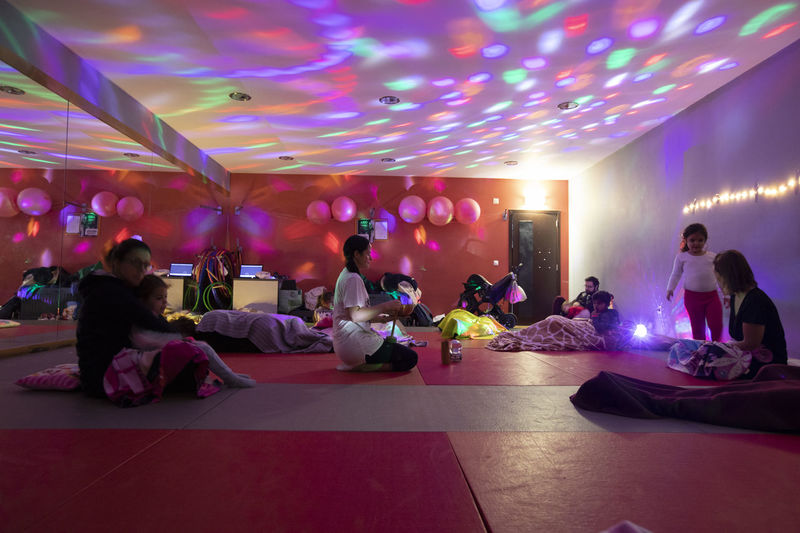Portugal; Aula de Yoga Yogagirl Group Of People Real People Illuminated Lifestyles Women Group Large Group Of People Leisure Activity Crowd Men Enjoyment Night Indoors  Party - Social Event Food And Drink Nightlife Adult Sitting Ceiling Disco Lights Dance Floor