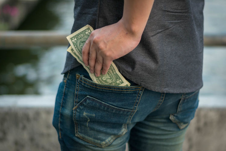 Midsection of man removing paper currency from pocket