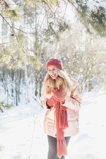 Smiling woman in warm clothing standing on snow